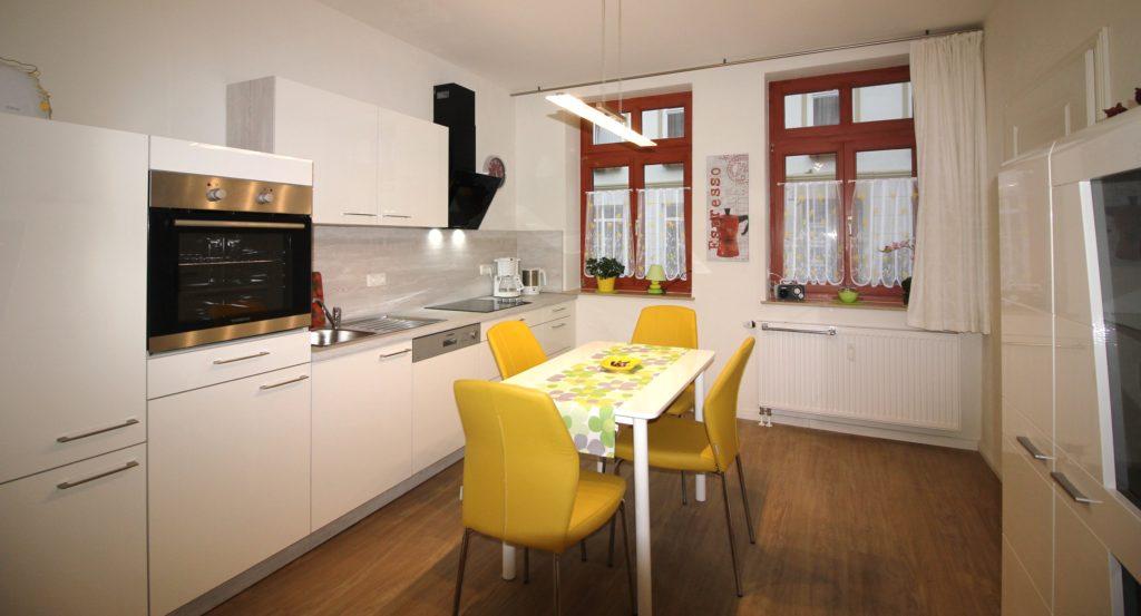 Küche der Ferienwohnung Wismar Altstadtblick mit Esstisch, Backofen, Ceranfeld und Abzugshaube