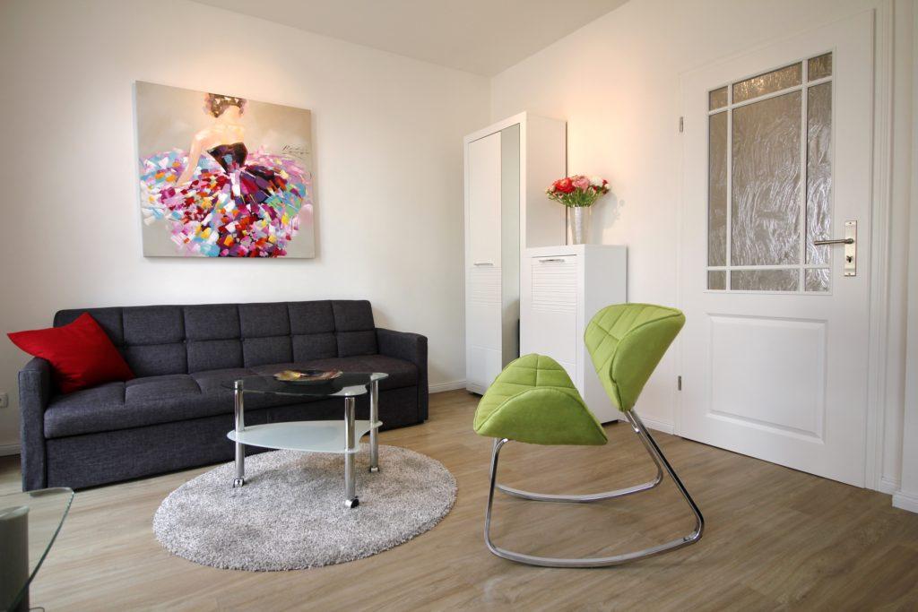 Wohn-/Schlafzimmer der Ferienwohnung Wismar Altstadtblick mit Fernseher und Sofa