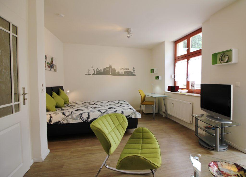 Wohn-/Schlafzimmer der Ferienwohnung Wismar Altstadtblick mit Fernseher, Sessel, Sofa und Sofatisch
